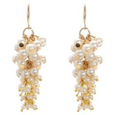An elegant addition to daytime outfits and evening ensembles, these bold hook earrings showcase clusters of faux pearls and gold-hued brass settings.