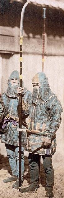 Samurai retainers wearing kusari katabira (chain armor jackets and kusari zukin (chain armor hoods), the man in front is holding a naginata.