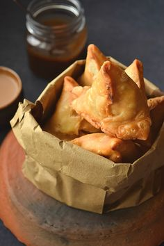 A top look of a brown paper bag having crisp fried Onion Samosa served with chai and date chutney Savory Snacks, Snack Recipes, Cooking Recipes, Easy Recipes, Curry Recipes, Vegetarian Recipes, Aperitivos Vegan, A Food, Food And Drink