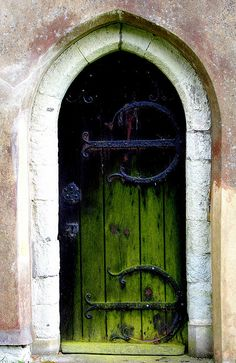 Arched green door with ironwork accents. I want to see what's behind it: I feel like fairies and witches must be in there. (Photo by Kim Rowley, at Wotton Church.)