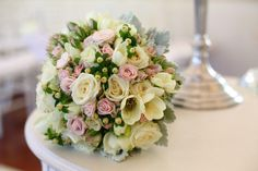 Sweet and classic, vintage bridal bouquet. Pale pink miniature roses, rosebuds, white freesias and white roses with a touch of silver dusty miller and hypericum berry. Dusty pink lace binding.