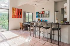 The dining room is open to the living room and kitchen. It has recessed lighting, Saltillo flooring, volume ceilings, and sliding glass door access to a side yard.#floridahomes #interiordesign #realestate #homedesign #homedecor #luxuryhome #designideas #palmbeachcountyhomes #palmbeachcountyrealestate #diningroom #diningroomideas #diningroomdecor #diningroomdesign