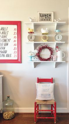 Country kitchen decorated for Christmas. Vintage hand painted sign. White open shelves with vintage scales, candycanes, wreath, an Elf on the shelf, and cow creamers. Flour sack made into a pillow sitting on a red chippy wood chair. Oh how I love red, white, & blue!