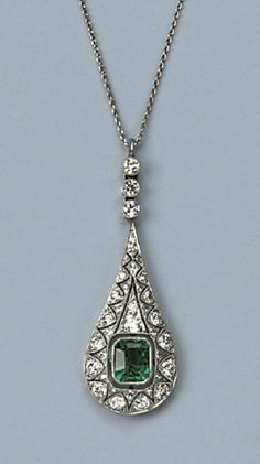 AN ART DECO EMERALD AND DIAMOND PENDANT   The pear-shaped openwork pendant set throughout with circular-cut diamonds, central step-cut emerald, on a fine chain, circa 1920, original case