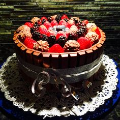I made 2 round red velvet cakes. I split each cake into halves to layer with chocolate ganache and another layer with custard cream. I covered entire cake with chocolate ganache so that kitkat chocolates could stick to it. I topped with fresh fruit and ferrero truffles.