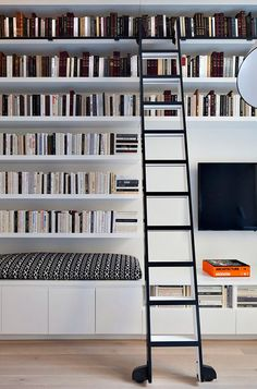white opening book shelves with modern black rolling library ladder / sfgirlbybay