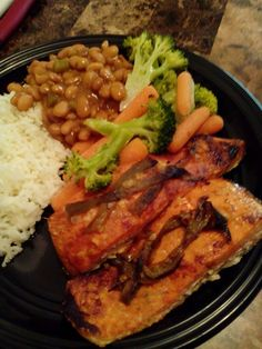 Spicy baked Salmon with veggies, beans and a little steamed rice. Healthy meal. Pescatarian meal.