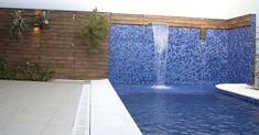 Pastilhas cerâmicas em diferentes tons de azul foram escolhidas para revestir essa piscina com pequena cascata de aço inox e projeto do arquiteto Celso Zuanazzi