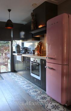 black kitchen with pink smeg fridge