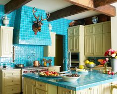 Handmade turquoise tile surrounds the range hood and doorways with hand hewn beams overhead