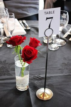Table centrepiece, red #roses, black linen, white stones.