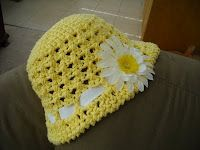free pattern for sun hat for girls. but with much wider brim. make with ecru color yarn and no flower. Thread a torn scarf through. can make to match sundress.