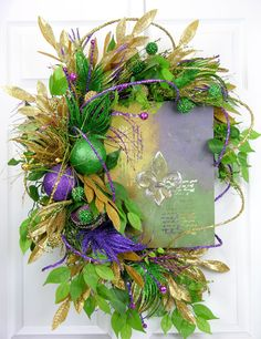 An exclusive MilandDil Design creation with a beautiful Mardi Gras canvas in a grapevine base wreath. This mixture of art and floral design draws you in to see the beauty of the Mardi Gras season. The