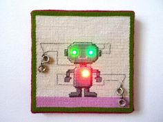Cutest Needlepoint Robot ever. Complete with conductive thread and light up LED eyes and a heart.