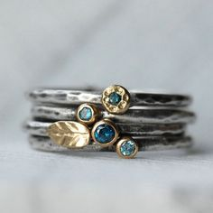 Questo elenco è per un insieme di quattro diamanti blu e blu zircone, oro 18k e argento foglia Anelli impilabili.  Diamanti blu scintillante teal teal e una luce aqua blu zircone impostare in ricco 18k oro gialle impostazioni. Un dolce piccolo 18 carati oro fiore è impostato con un diamante scintillante teal blu, e una dolce piccolo 18k oro foglia completa linsieme.  Dettagli: Diamanti - Conflict free, 1.7 mm, 2 mm e 2,5 mm - teal blue Blu zircone - 2mm Argento e oro - ecologico, riciclato…