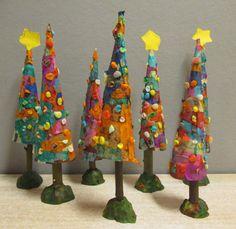 Kerstboompjes van kegelvorm van papier, daarop stukjes vloeipapier geplakt en versiert met van die maisknutseldingen in schijfjes geknipt. De boom op een stok in de klei. Nutsschool Maastricht