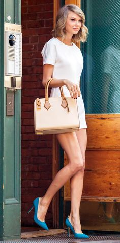 Taylor Swift stepped out in a structured white top and matching shorts while in NYC. She accessorized the look with bright turquoise SJP Collection shoes and a neutral Michael Kors handbag.