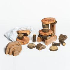 Blocs de fusta polida amb l'escorça, de mides i formes diverses, amb un costat llis per fer-les apilables.
