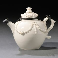 Mennecy White Glazed Porcelain Teapot and Cover, France, c. 1740, globular shape with faceted spout and scrolled foliate handle, the body applied with foliate festoons, the cover with floral knop