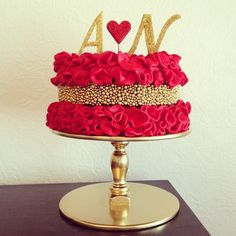 Red & Gold Ruffle Cake.   The gold cachous' were rolled in gold lustre powder mixed with a drop of clear white spirit to get the antique gold colour required.  Once dried they were individually stuck on.   Each ruffle was made of red fondant cut with a circular cookie cutter and then pinched into a ruffle.  I mixed bought bright red fondant  with rose gel paste to get this colour.  I made the letters and heart using gum paste and edible glitter.