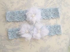 "Garter in blue and white.  We have other colors available (peachy blush, white, pale pink, tiffany blue) to coordinate with your wedding colors.  I made this with  piece a 1 1/ 2"" wide stretch lace (very soft and comfy.) The bridal garter is made with 2 layered tulle flowers and attached to a pale blue lace garter. The toss garter is made with one tulle shabby chic flower tulle flower.  It will be delivered in a beautiful white organza gift bag with a beautiful satin tie. Perfect for gift..."