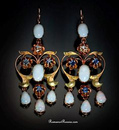 Elegant Antique Russian Jeweled Girandole Earrings, made in St Petersburg between 1908 and 1917. The earrings are formed  as sprays of flowers centered  with 8 mm milky white opals cut en cabochon with  two rose-cut diamonds and six  step-cut sapphires, within stylized matted green gold scrolling leaf  frames, with three suspended drop-shaped cabochon opal pendants, all  claw-set.   Length 2 in. (5,2 cm)