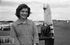 Jackie is leaning against the back end of an airplane while campaigning with Senator Kennedy.
