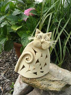 Kočka - svícen Kočka ze šamotové hlíny. vhodná do interiéru i na zahradu. Výška 19 cm. Svíčkou se nahřívá a sálá teplo.