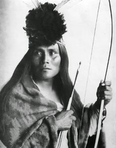 Apache Indian photographed with head dress and bow and arrow in 1914