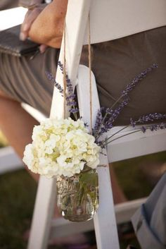 {hang jars of flowers from the chairs}