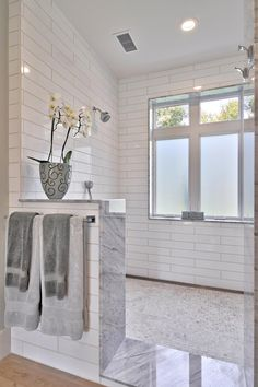 Classic white subway tiles and a small potted plant bring farmhouse charm to the elegant materials and modern design of this clean master bathroom.
