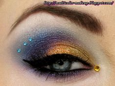 Pretty gold, purple and blue eye shadow accented with small aqua crystals and a single gold crystal.