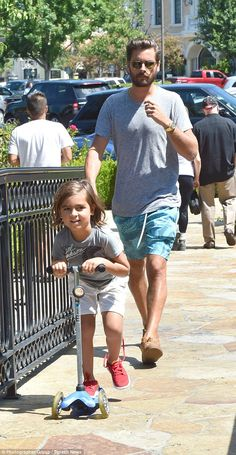 Kid's chic: Meanwhile his son was in a grey T-shirt with a striped pattern, and pushed his...