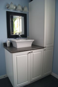 Linen closet, vessel sink and trough faucet make the vanity in this bathroom renovation truly unique.