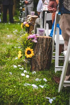 Alternative aisle décor with flowers at base of stump, also could have B&W photos of bride, groom and wedding party in silver frames sitting on each stump