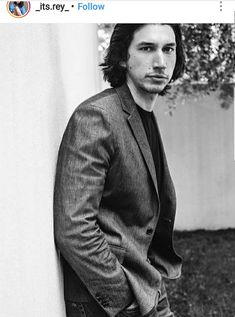 Youngish Adam Driver looking debonair in a grey suit and black shirt, black and white photo. From _its.rey_