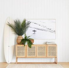 home accessories living room Beautiful beachy vibe with a cane console table in light wood, vertical white shiplap, large wall art, plants, and a surfboard! Retro Home Decor, Home Decor Accessories, Interior, Living Room Playroom, Beach House Decor, Handmade Home Decor, Living Room Decor, Home Decor, House Interior