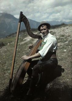 A young man plays a harp while wearing the national costume of Tyrol, ca. October 1928 in Arzl im Pitztal.