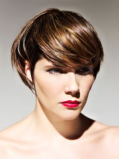Short brunette razor haircut with full side swept bangs and blonde highlights