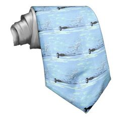 Floating Ducks Necktie. This very simply designed tie features a repeating pattern of silhouetted ducks moving across the water, leaving a wake of ripples behind. The minimal colors are pale blue, gray, white, turquoise, green and black.