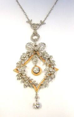 Edwardian platinum and diamond necklace. It has the lovely, intricate garland look that Edwardian jewelry is known for, and also incorporates a surprising touch of enamel. This particular piece is not by Cartier, but the renowned jewelry house popularized the garland style, using laurel leaves, flowers, ribbons and bows to create light, delicate designs resembling lace.