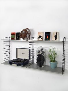 Mid-century modular shelving from Tomado - original Dutch Design. The grey metal shelves are deeper than the shelves of an ordinary wall rack, and thus can accommodate for example a Crosley. You can hang the shelves at any height in the rack.