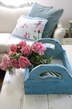 Blue wooden carrier decorated with pink flowers as a centerpiece.