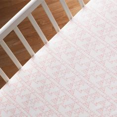 Tiny triangles give off a subtle Aztec vibe on this pale pink crib sheet. #nursery