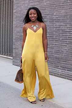 Casual, chic street style look featuring a satin yellow jumpsuit. | essence.com