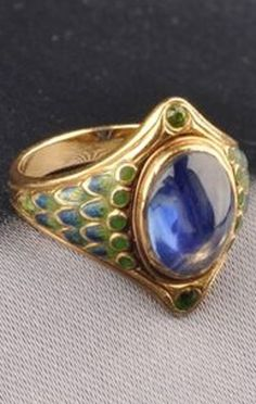 Art Nouveau Sapphire, Demantoid Garnet, and Enamel Ring, Tiffany & Co. Bezel-set with a cabochon sapphire framed by circular-cut garnets, shoulders with graduating green and blue basse-taille enamel accents, incised shank with enamel highlights, signed. #Tiffany #ArtNouveau #ring