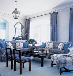 Black accents ground the blue-and-white scheme in this living room in Ponte Vedra Beach, Florida.  Designers Jim and Phoebe Howard adorned the sofa and windows in an exuberant print by Charlotte Moss and underscored the range of blues at work with an antique dhurrie rug.