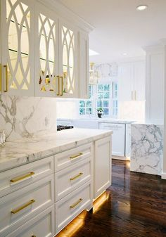 Kitchen trends: side attached butler pantry, gold accents, all white cabinets and stunning marble counters! Lets not forget the trend of accent lighting within cabinets and under cabinet lighting!