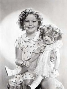 1936 Shirley Temple autographing a Shirley Temple Doll for some lucky fan!