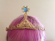 My princess bubblegum crown! One cheap circlet plus some filigree bits and one blue gem equals radical fancy-ness.Here is my how it was made/where to find components: I used a gold circlet similar to this one as a base: http://www.elope.com/estylez_item.aspx?item=110130That one is from the same brand as mine, Elope, which is cheap and carried at a lot of costume stores. I found mine at the local specialty costume shop. I have the advantage of living in a city where these specialty things…
